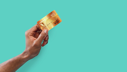 Male hand holding golden credit card on blue background
