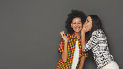 Fototapeta Young woman whispering to her friend against grey background obraz