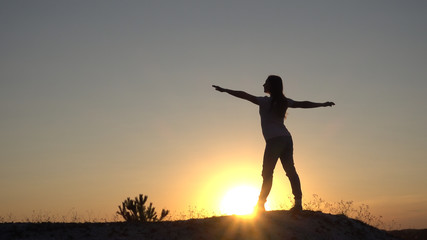 Silhouette young woman practicing yoga and Meditation at sunset