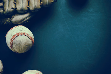 Baseball ball with glove on dark background with grunge texture, old and used from sport game.