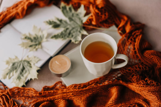 autumn fall concept, notebook, red scarf, autumn leaf, candle and cup of hot tea, hygge