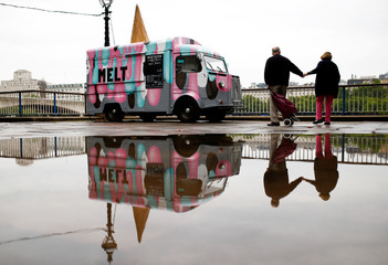 People are reflected in a puddle as they walk past a closed ice cream stand on the South Bank in London