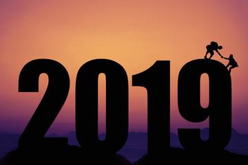 Neues Jahr 2019 Silhouette mit Bergsteiger bei Sonnenuntergang