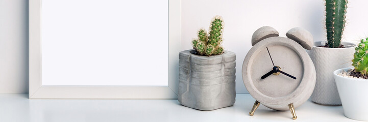 Panoramic photo of white mockup frame with cactuses and a round concrete clock on a white background