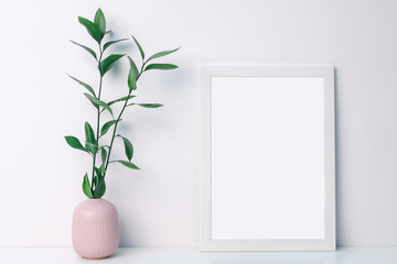 White frame mockup with a pink notched vase with twigs with green leaves on an empty white background