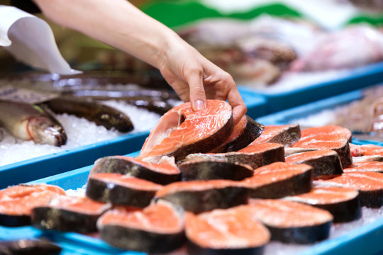Young seller choosing a peace of salmon in the market.