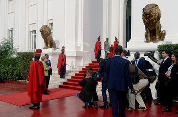 German Chancellor Angela Merkel poses for pictures as she is greeted at the Presidential Palace by Senegal's President Macky Sall in Dakar
