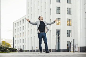 Distant plan of happy man raising his arms while going to or from work.