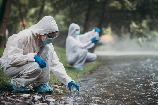 Two scientists in protective suits taking water samples from the river.
