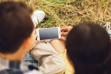 Shot of boy and girl using phone taken from above. Two little kids sitting on grass in park and starring down at smartphone screen.