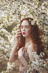 Portrait of A gentle woman with long red hair in a blooming spring garden. Red-haired sensual girl with pale skin and blue eyes with bright unusual appearance.