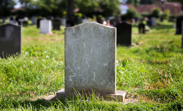 Blank gravestone with other graves and trees in background. Old stone.