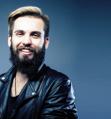 portrait of young bearded hipster guy smiling on gray background