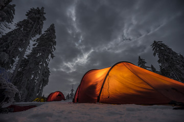 Winter camping, night, shining red tent on snow, clouds, forrest. Night shot, long exposure, sleeping on snow in the outdoors.