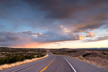 Highway curving into the distance through the landscape near Santa Fe,  New Mexico underneath a dramatic colorful sky at sunset