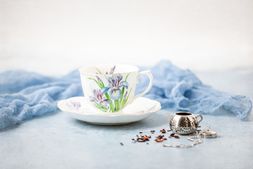 Royal Albert Iris Fine Bone China Tea Cup and Saucer with Herbal Tea and Tea Infuser on Blue Background