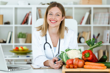 Beautiful smiling nutritionist looking at camera and showing healthy vegetables in the consultation.