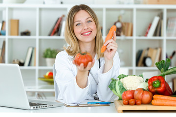 Beautiful young nutritionist looking at camera and holding fresh vegetables in the consultation.