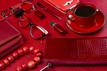 Woman red accessories with coffee, cosmetic, jewelry, gadget and other luxury objects on leather background, fashion industry, modern female concept, selective focus