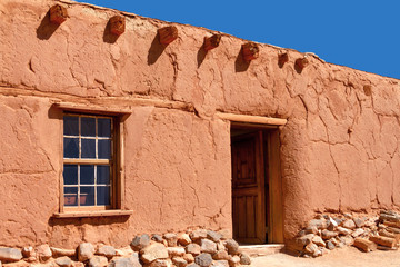 Rustic Santa Fe style adobe building with window door
