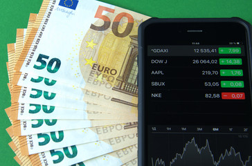 European Euro banknotes and smartphone, mobile trading.