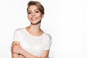 Portrait of lovely blonde in white t-shirt. Attractive girl with perfect make-up and trendy hairstyle standing and looking at camera with gladness
