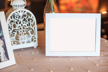 Blank wooden picture frame decoration on table decorated by white tablecloth. Wedding reception ceremony, anniversary celebration, interior concept.