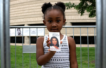 A young girl holds a card of Aretha Franklin outside the Charles H. Wright Museum of African American History on the second day of a public viewing of the late singer in Detroit
