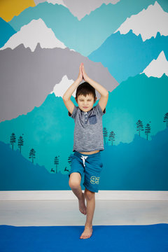 Cute caucasian child does yoga in his room with a beautiful mountain mural.  vrksasana Tree Pose yoga position