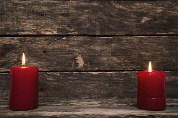 Burning candle on aged wooden table background.