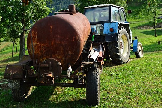 Older Czechoslovak agriculture tractor with rusty water tank trailer , viewed from rear side in summer sunset.