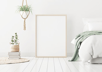 Poster mockup with wooden vertical frame standing on floor in bedroom interior with bed, green plaid and plants on white wall. 3D rendering.