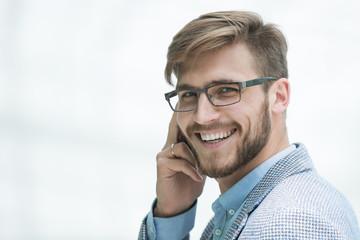 close up.smiling businessman talking on smartphone
