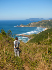 Woman taking picture from Galheta and Mole beach, popular beaches in Florianopolis, Brazil