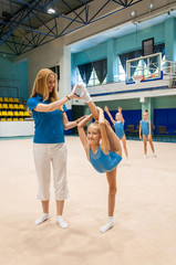 Coach teaching little gymnast
