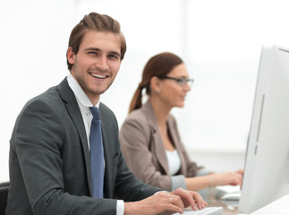 close up.smiling businessman with an assistant at the Desk