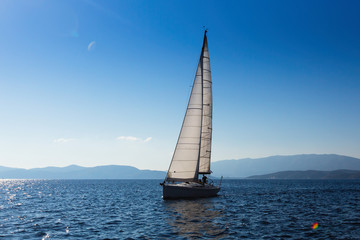 Sailing yacht with white sails in the Sea near Greece coast.