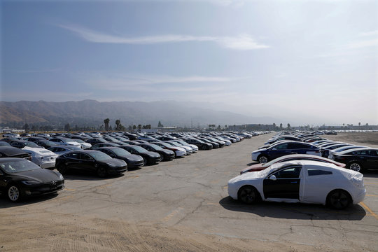 Newly manufactured Tesla vehicles are shown parked in a large lot next to the airport in Burbank, California