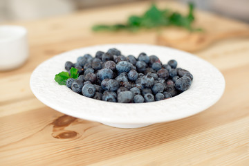 Blueberries in a white plate on a wooden table.