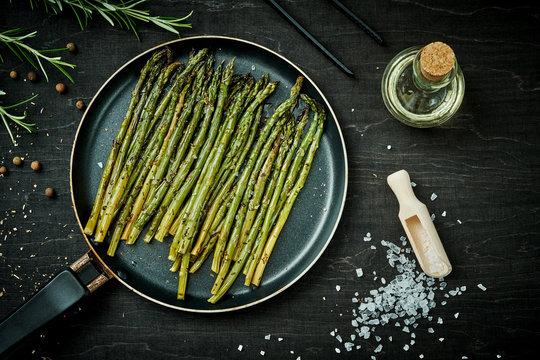 delicious green asparagus in a pan on a wooden black table with rosemary salt and olive oil
