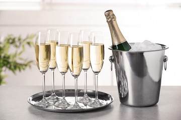 Glasses with champagne and bottle in bucket on table indoors