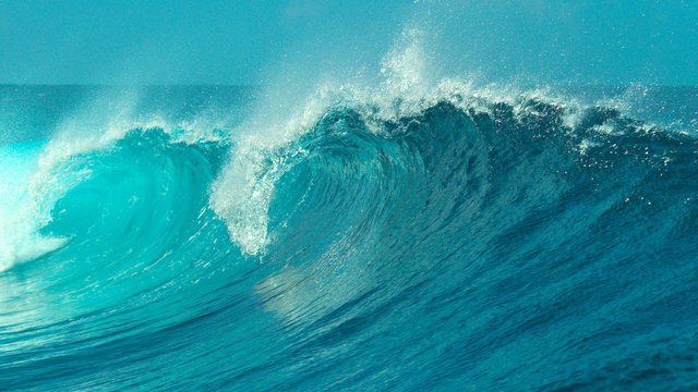 CLOSE UP: Glimmering barrel wave rushes past the camera on a sunny day in Tahiti