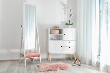 Stylish living room interior with chest of drawers and mirror