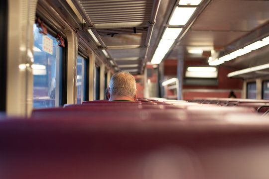 Back of Man's Head Sitting In A Seat On A Commuter Train.