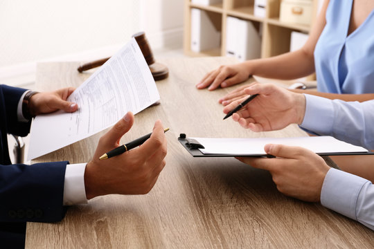Lawyer working with clients at table in office, focus on hands