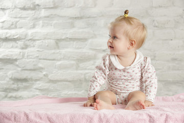 Portrait of a cute baby girl sitting in the room
