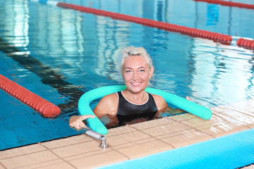 Sportive senior woman with swimming noodle in indoor pool