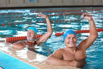 Sportive senior men doing exercises in indoor swimming pool