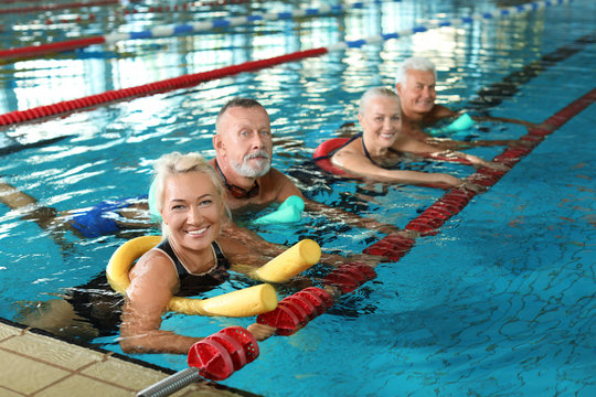 Sportive senior people doing exercises in indoor swimming pool