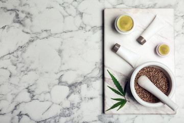 Flat lay composition with hemp lotion and space for text on marble background